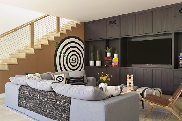 basement furniture with gray sectional, tv, and dart board