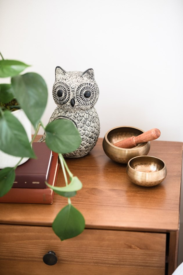 meditation bowls on wood table with ceramic owl