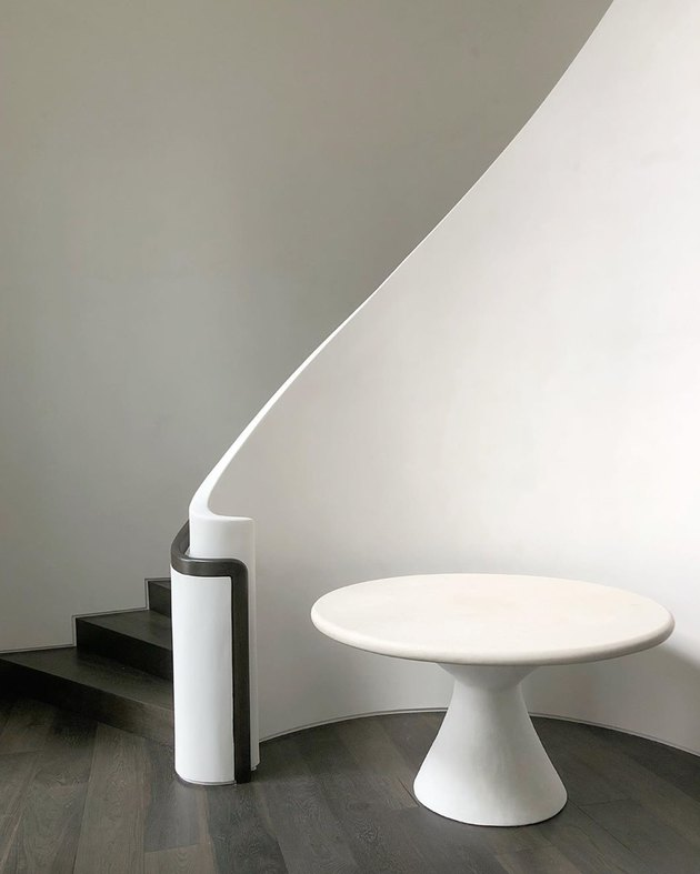 solid poured plaster banister with black stair railing
