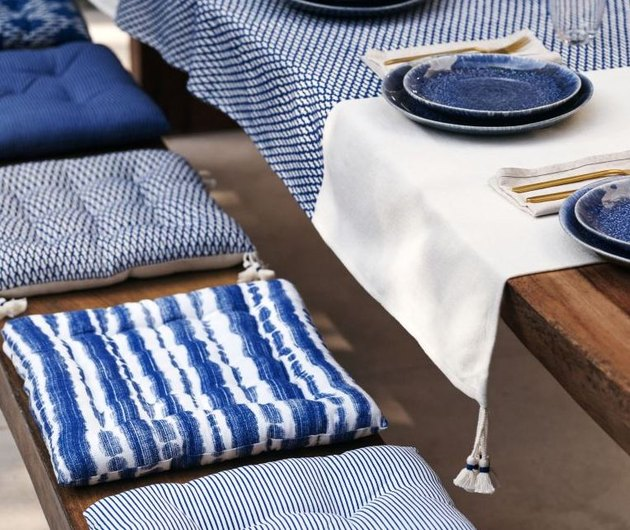 outdoor table with seat cushions, linens, and blue plates