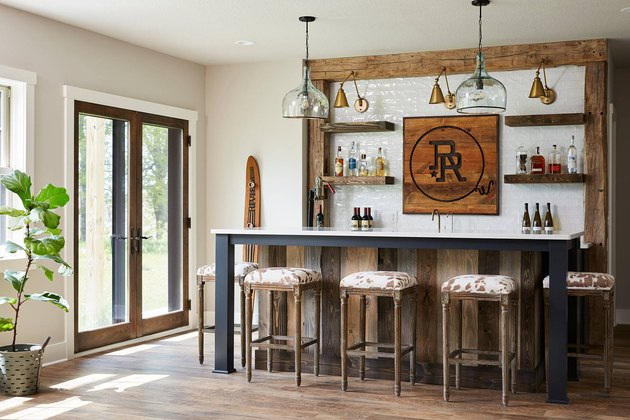 rustic basement bar with subway tile backsplash and cowhide stools