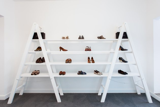 A white bookshelf against a white wall with shoes