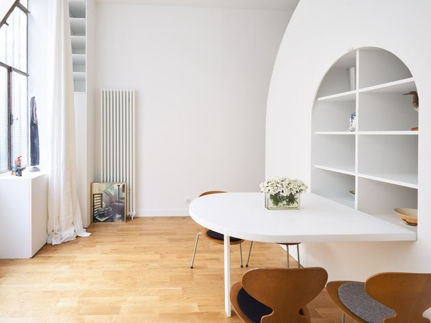 half-circle fold-out dining table in all-white living room