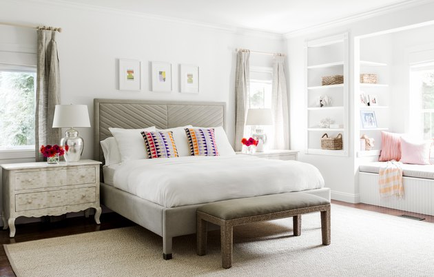 traditional neutral bedroom idea with white walls and colorful throw pillows