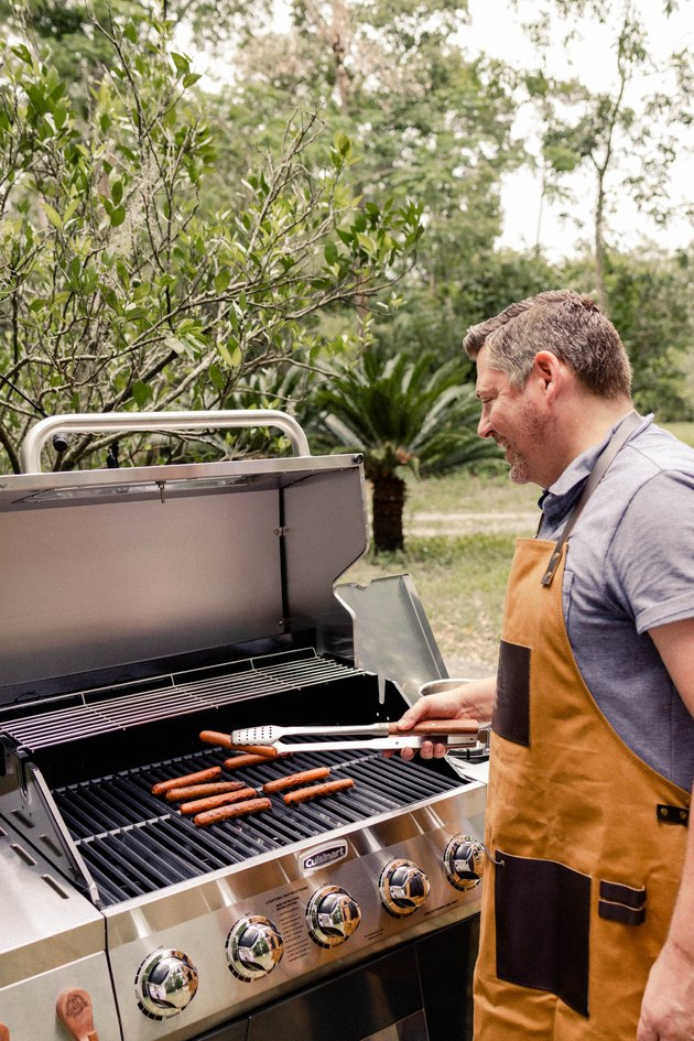Man grilling hot dogs at Cuisinart grill wearing tan and leather Pit Boss apron