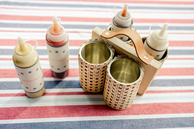 DIY condiment caddy made from four soup cans wrapped in cane webbing and attached to board with handle