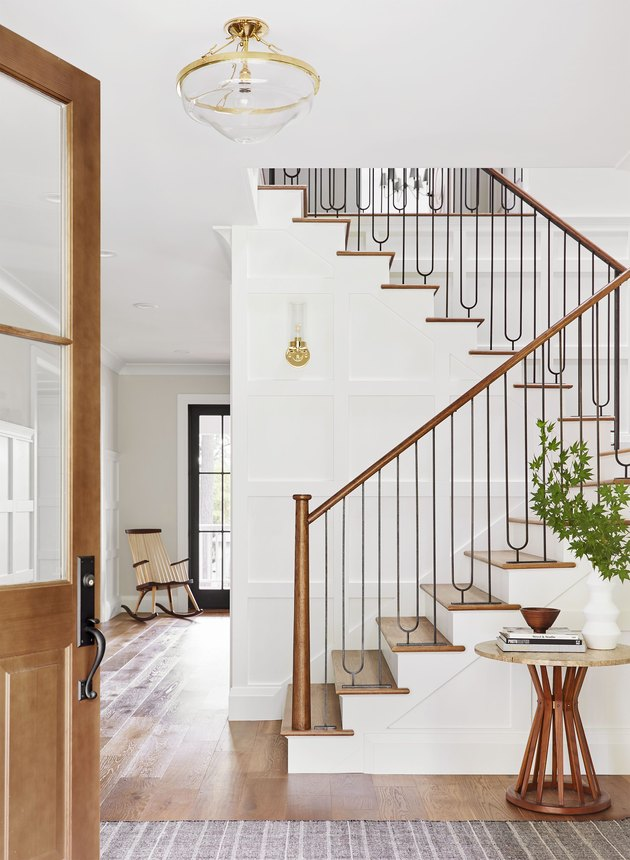 traditional staircase with metal spindles and wood stair railing