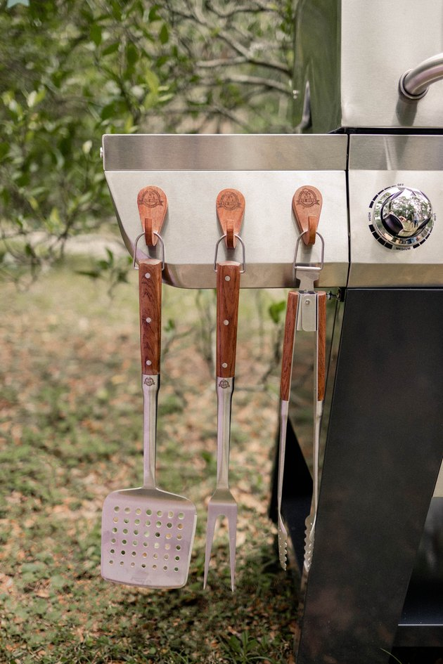 Three wooden Pit Boss magnetic hooks hanging from grill with BBQ tools hanging from them