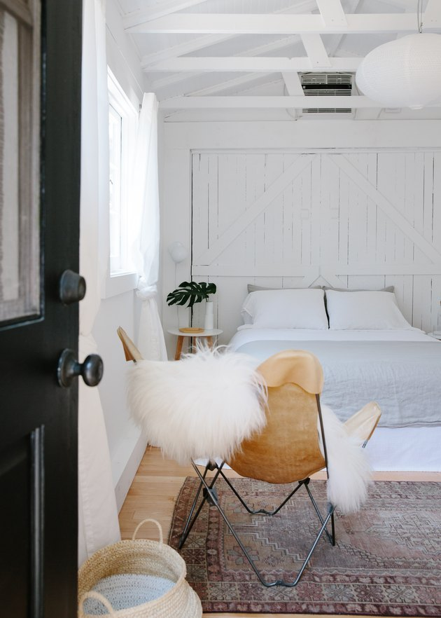 black front door opening to minimal boho bedroom