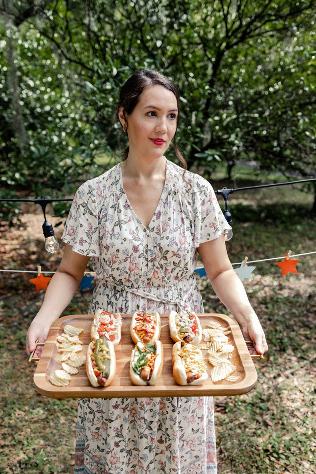 Woman holding wooden tray with six gourmet hot dogs and potato chips