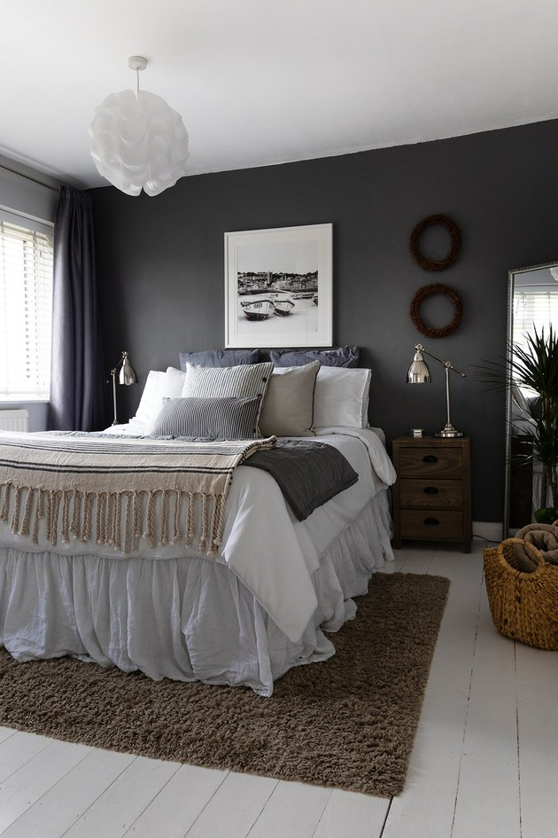 neutral bedroom idea with dark gray walls and drapery