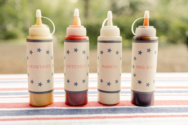 Four hot dog bar condiment bottles with printable labels for mustard, ketchup, ranch, and BBQ sauce