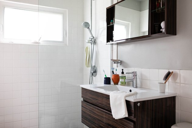 surface-mount wood medicine cabinet with mirror in the center, brown vanity with white ceramic top, white tile shower with glass door