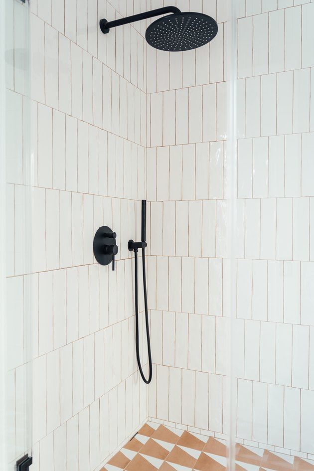 glass shower door with white vertical tiles, black shower head and fixtures, tile floor with orange triangular pattern