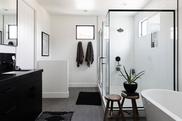 large bathroom with freestanding white tub, two wooden stools, black vanity, glass shower with black trim, two towels hung up, wood flooring