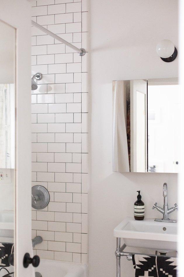 white ceramic console sink, mirrored medicine cabinet, white subway tile shower wall, round white light fixture