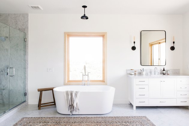 large bathroom with freestanding white tub, glass shower with large marble tile, rectangular window, black pendant light fixture, white vanity with marble top, rectangular mirror with black trim, two black sconce light fixtures, brown area rug