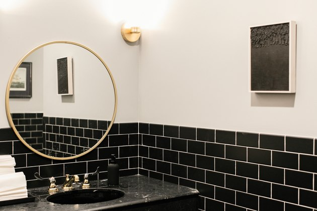 black subway tile wall, black vanity with gold fixtures, gold round mirror, rectangular artwork with black interior