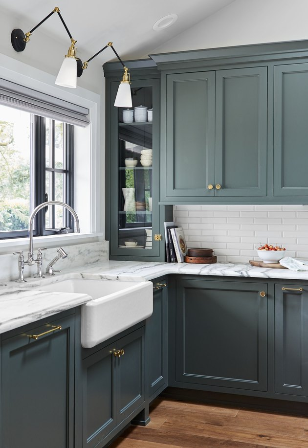 green kitchen cabinet hardware idea with brass pulls and marble countertops