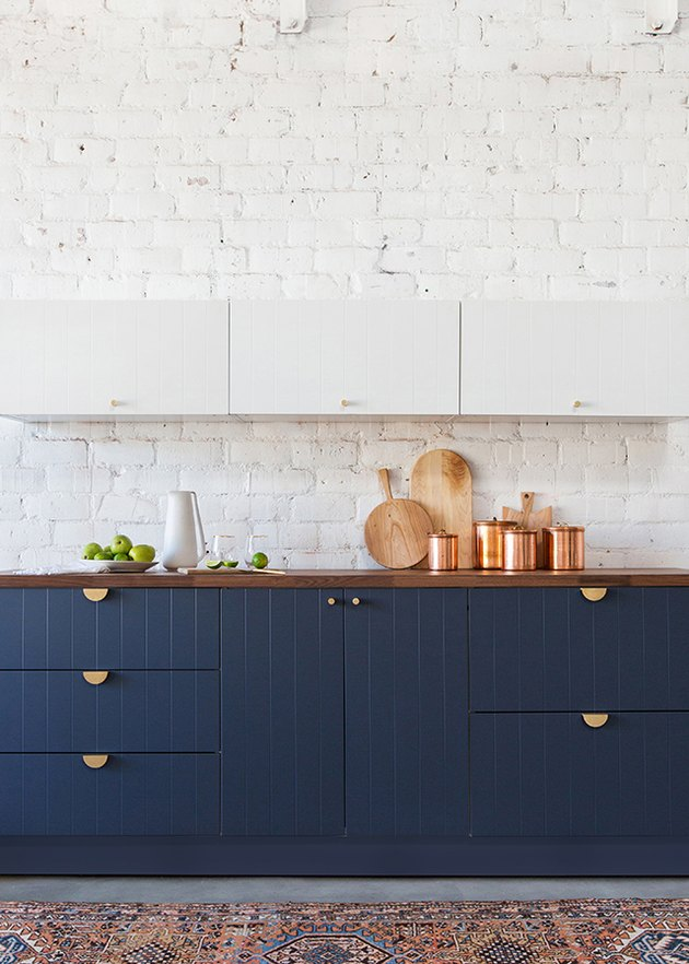 kitchen cabinet hardware idea with blue cabinets and whitewashed brick walls