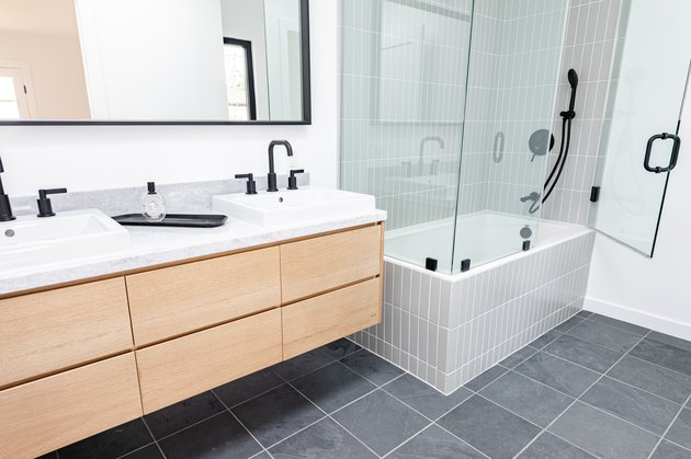 light wood floating vanity with two ceramic vessel sinks, black faucets, rectangular mirror, gray square tile floor, white tub with glass shower doors