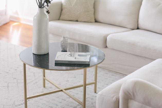 Coffee table with gold painted legs and green faux marble top.
