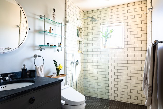 black vanity with black stone countertop, round mirror, white toilet, glass over-the-toilet storage shelves, white subway tile shower wall, glass shower door, window in the shower