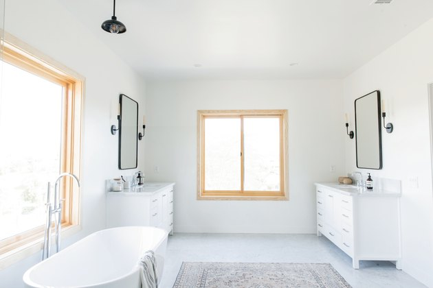 freestanding white tub with silver faucet, double vanities on opposite sides of the bathroom, matching rectangular mirrors with black trim, two windows, multicolored area rug, black pendant light fixture