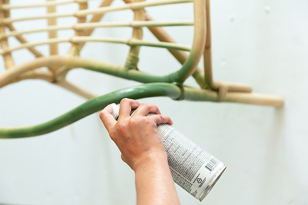 Spray painting rattan chair with green paint.