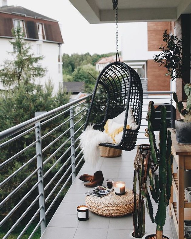 bohemian balcony idea with black hanging chair and woven floor pouf