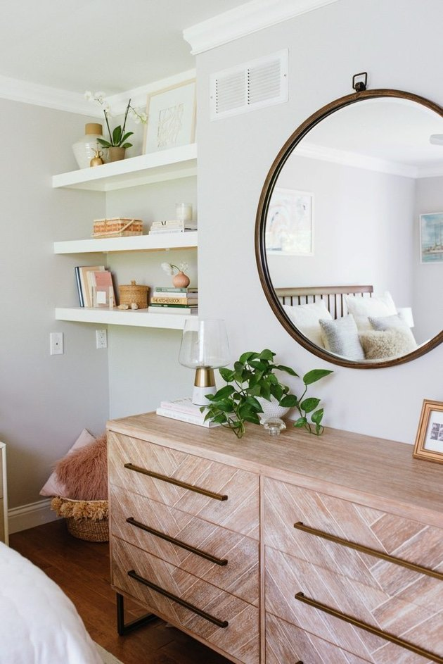 Bedroom shelving idea with modern wood dresser and large round mirror