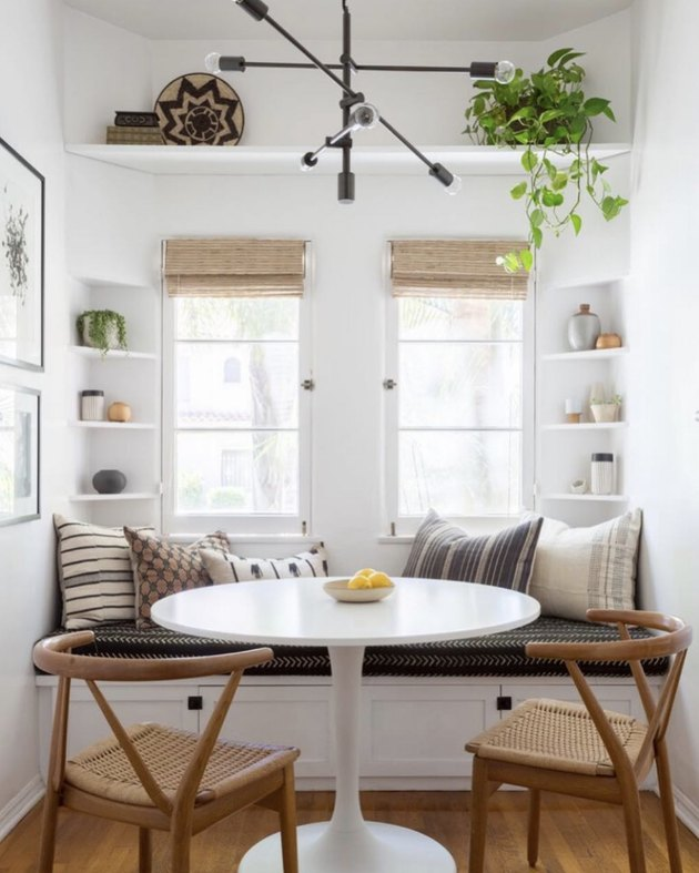 Kitchen nook idea with white tulip table and light wood wishbone chairs in a modern, bright kitchen nook