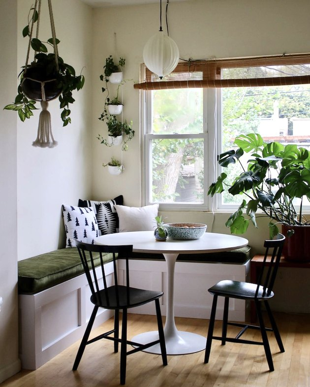 Kitchen nook idea with white tulip table and black bistro chairs in a kitchen nook with lots of plants