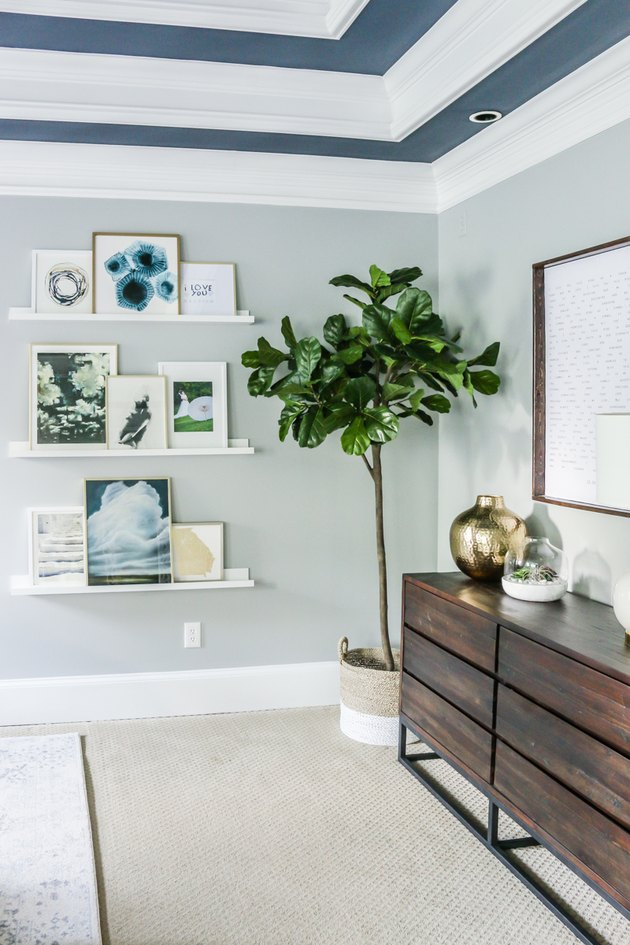 blue bedroom shelving idea with gallery wall and painted ceiling