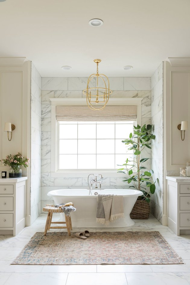 traditional bathroom idea with marble tile, creamy cabinets