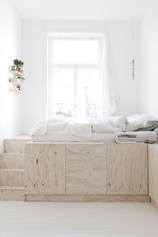 studio bedroom idea with a tall bed built out of plywood with storage underneat and stairs to the left. White bedding is on top.