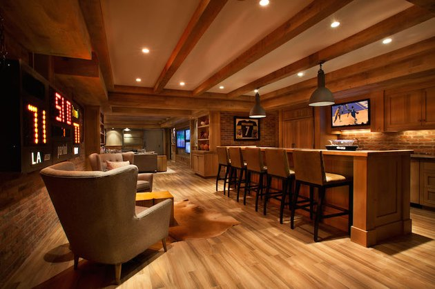 basement man cave ideas with exposed wood beams and bar