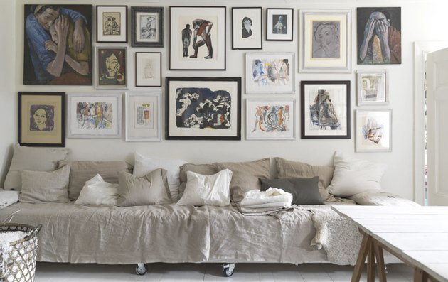 studio bedroom idea with two twin beds placed end to end covered by a beige sheet to create a long seating area, a gallery wall hangs above