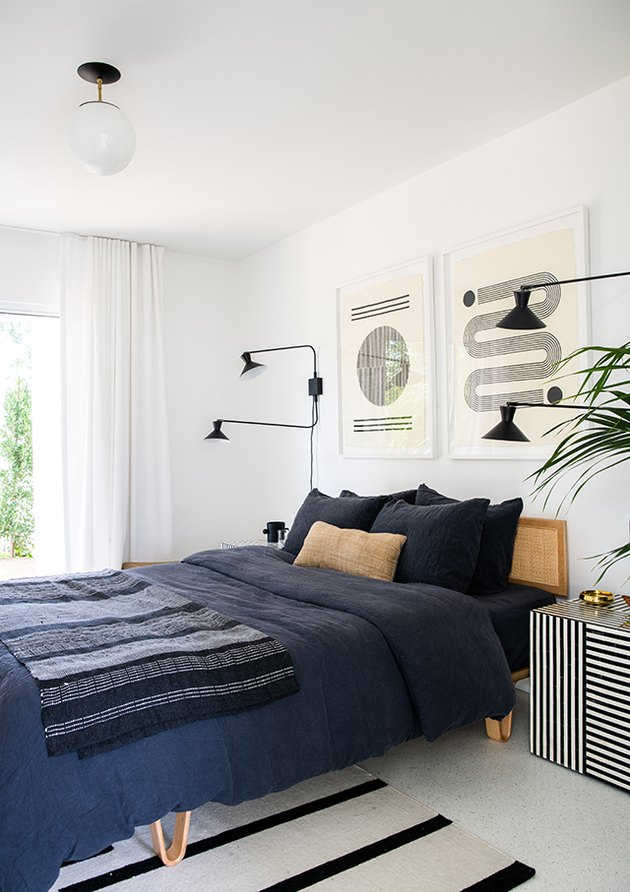 black and white bedroom idea with graphic striped prints and navy blue accents