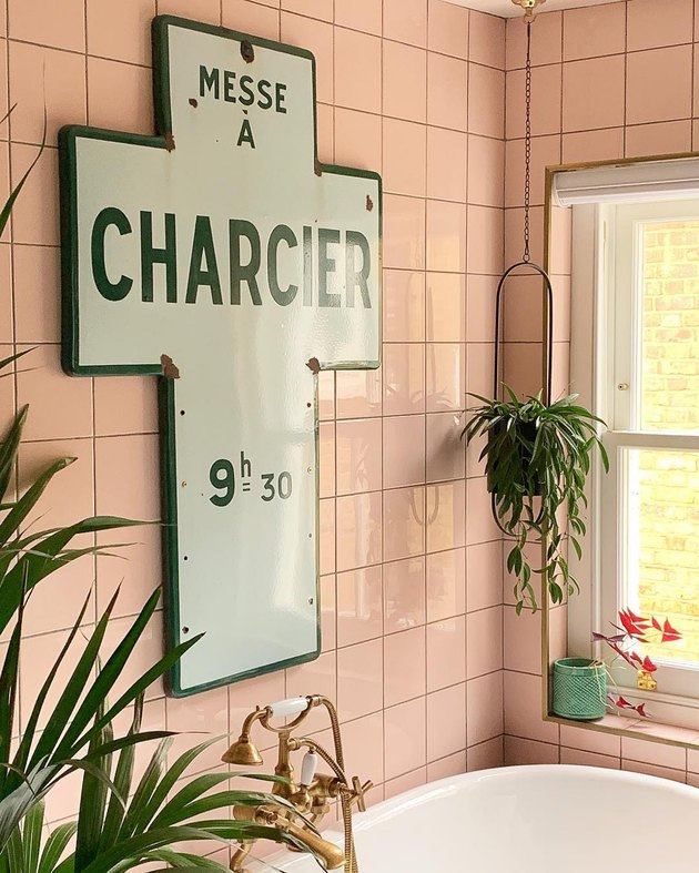 bathroom design idea with pink wall tile and vintage church sign