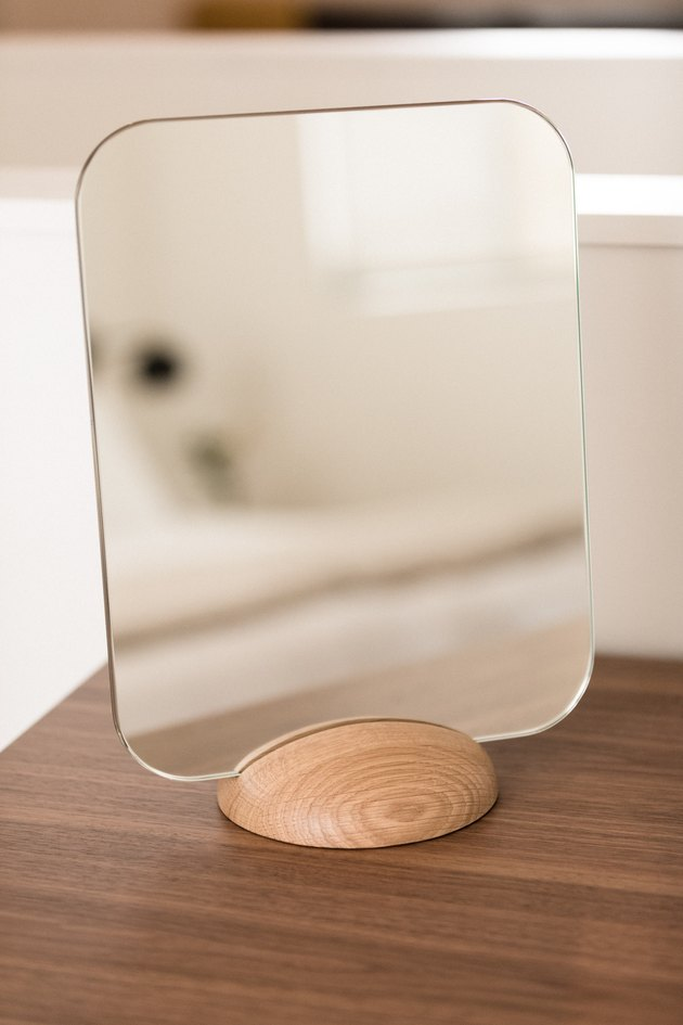 minimal table mirror with light wood base on a dark wood console