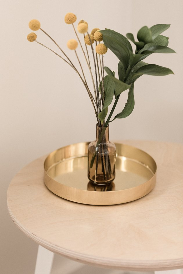 brass metal tray with glass vase holding billy balls
