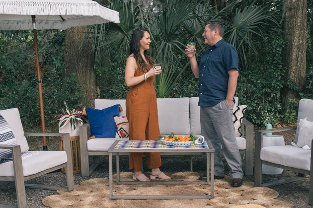 Woman and man standing in outdoor patio with DIY tiled coffee table, colorful pillows and fringe umbrella