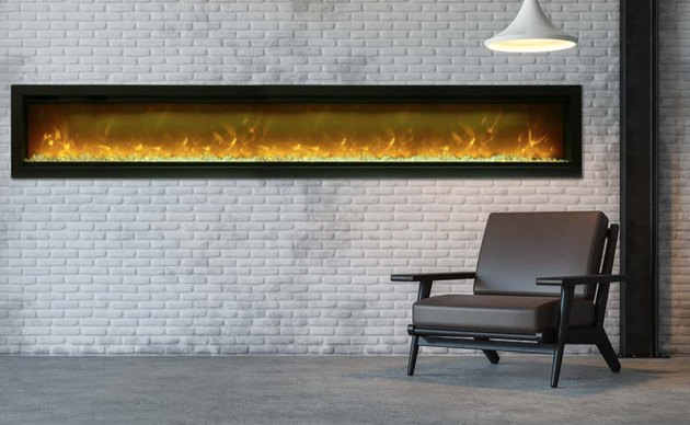 long basement fireplace set in white brick wall with hanging pendant