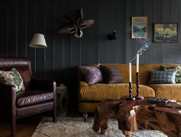 black basement wall ideas in cabin with leather chair and tree stump coffee table