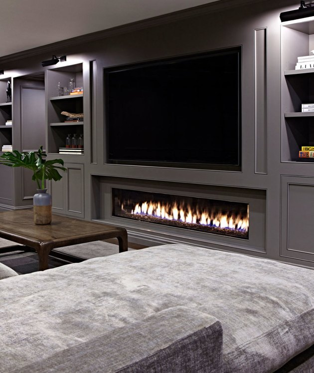 basement fireplace and mounted TV with gray sectional and gray walls