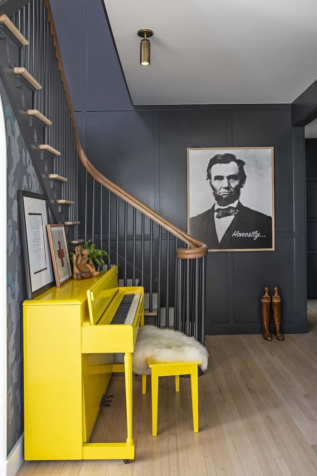 black stair railing with wood banister next to yellow piano