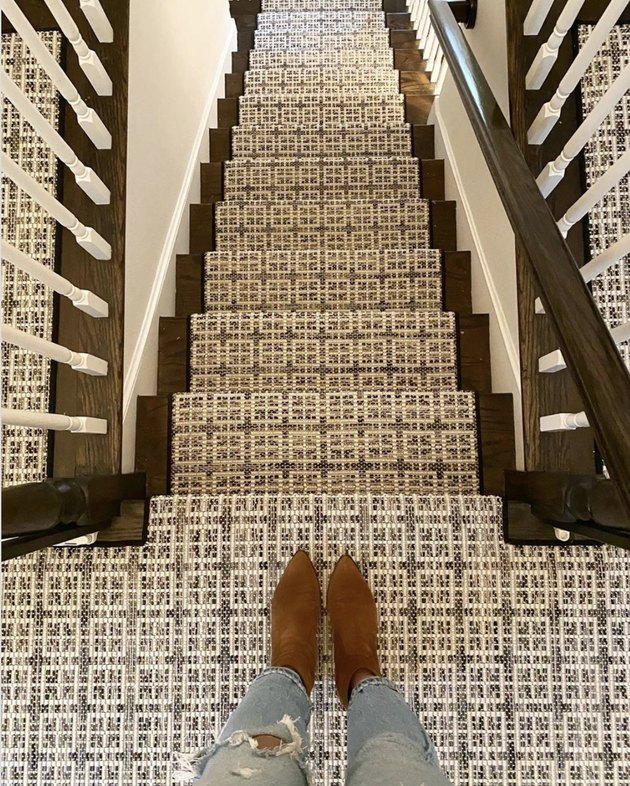 Woven stair runners on dark wood stairs with white spindles