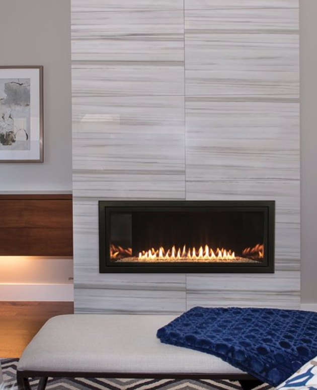 modern basement fireplace with neutral mantel and blue throw blanket