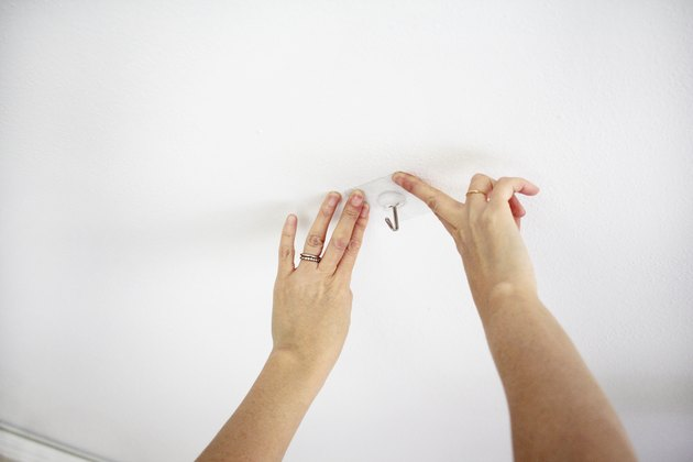 Pressing an adhesive hook onto the ceiling